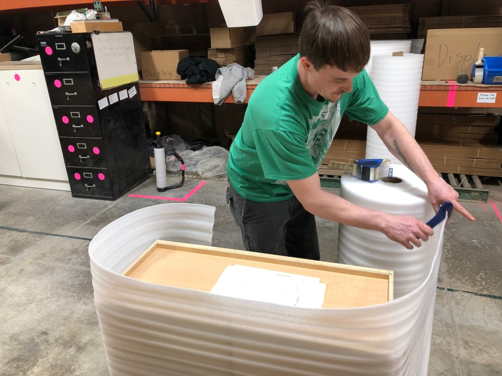Chaz wraps a completed cabinet in foam and shrink wrap