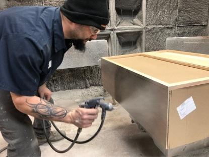 Jon sprays a cabinet